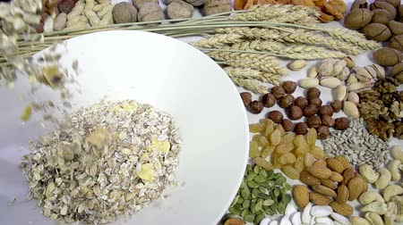 kurutulmuş : In the bowl of muesli backfilled against the background of a variety of dried fruits and nuts. Slow Motion