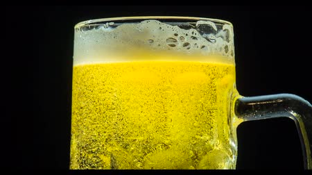 The large glass mug with beer slowly rotates in front of camera on a black background. Slow Motion 120 fps