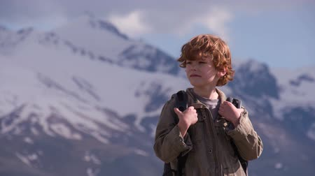 boletim informativo : Curly red-haired boy with a backpack explore the area on a background of snow-capped mountains Stock Footage
