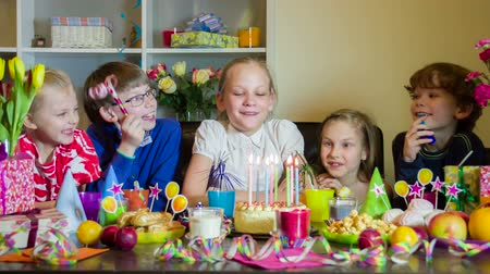 cakes : Girl makes a wish and blows out a candle on a birthday cake. Friends around fun react
