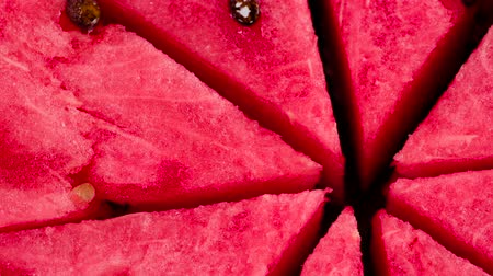 Sweet Summer Treats. Video Loops. Triangular slices of watermelon rotate in front of the camera.
