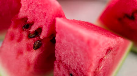 Juicy Watermelon Triangles. Triangular pieces of watermelon are on a rotating fruit plate. Camera looks sideways down