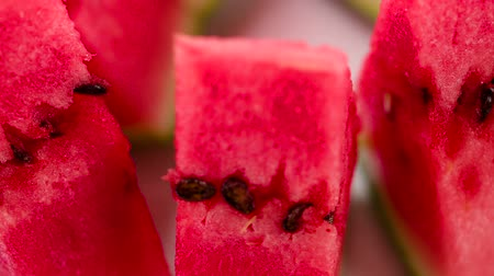 section : Juicy Triangular Pieces of Watermelon. Video Loops. Triangular pieces of watermelon are on a rotating fruit plate. Camera looks sideways down Stock Footage