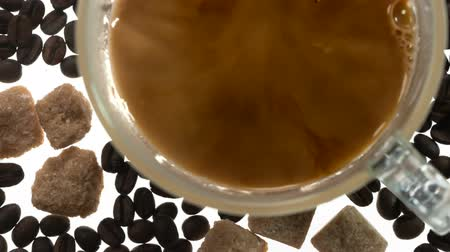 Cup of Morning Coffee with Milk. View from above. Milk is poured into a transparent cup of coffee. The cup stands on a bright white table among coffee beans and pieces of sugar Stock mozgókép
