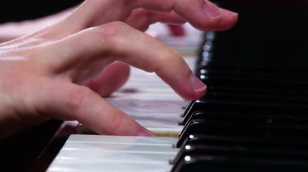acoustic : Jazz Melodies on Piano. Female fingers close-up, slow, the piano keys, extracting a simple melody. Filmed at a speed of 120fps