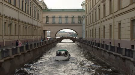 St. Petersburg, Russia, August 07. 2017. View of the Hermitage Bridge. The pleasure of the boat is moving along the canal Winter Canal towards the Neva
