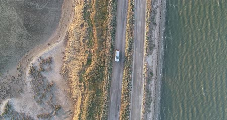 4K aerial drone view of Azov liman coastline. Offroad car driving on Azov sea coast at sunset