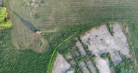 An aerial view of a man cutting his lawn with a riding mower.