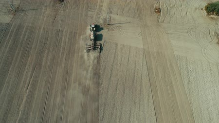 hay harvest : Aerial: Lonely tractor plow the wheat field
