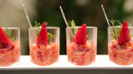 стартер : Fresh salad with strawberry and salmon in glass. Camera moves from side.