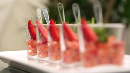 Fresh salad with strawberry and salmon in glass. Camera moves from side.