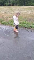 raincoat : Little girl jumps in rubber boots in a puddle.