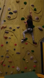 bouldering : Young girl, age 7, climbing on a climbing wall. Stock Footage
