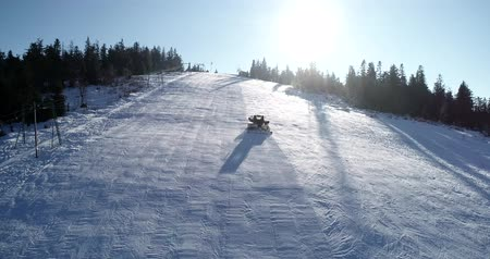 snowcat : Aerial top down view of a snowcat or snow groomer on a ski resort slope in winter