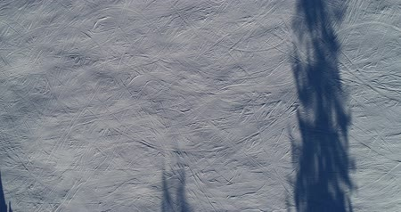 ski run : A beautiful aerial shot of people skiing in a snowy mountain ski resort.