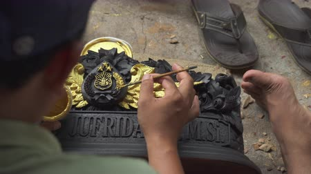 indonésio : Asian wood carver paint. Wood carving workshop Bali - October 2017: Sukawati, Bali, Indonesia