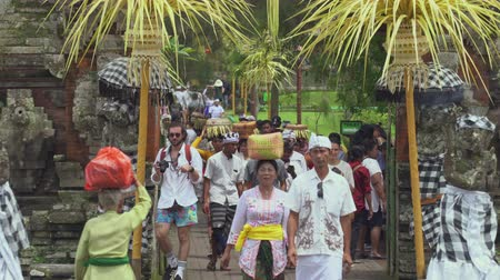 sacrifício : Balinese women carry offerings on their heads at Taman ayun temple - October 2017: Mengwi, Bali, Indonesia Stock Footage