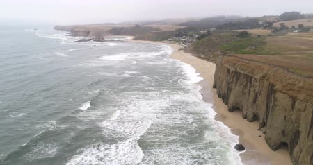 államközi : Flight over of steep rocky coastline, waves crashing cliffs - California Stock mozgókép