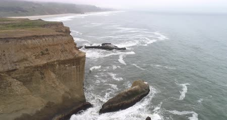 barışçı : Flight over of steep rocky coastline, waves crashing cliffs - California Stok Video