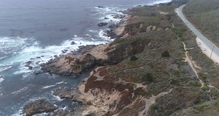 íngreme : Flight over of rocky coastline. Aerial view of Ocean shore, California state route 1