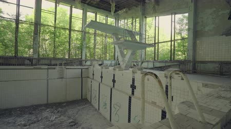 атомный : Abandoned swimming pool building in Pripyat. Chernobyl nuclear disaster. Slider shot - Juni 2017: 30km Chernobyl, exclusion zone Стоковые видеозаписи
