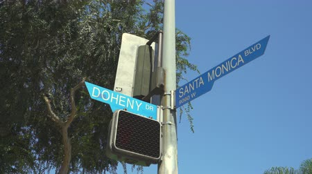 verkeersbord : Santa Monica Blvd, Doheny-straatteken. Schuifregelaar - augustus 2017: Los Angeles, Californië, VS. Stockvideo