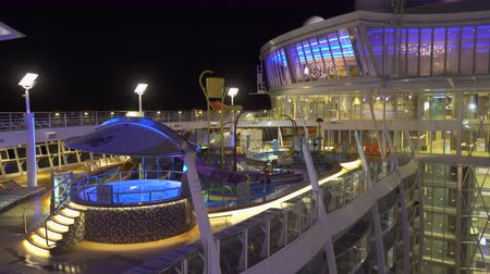джакузи : Illuminated cruise ship pool deck at night - Harmony of the Seas Стоковые видеозаписи