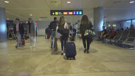 follow shot : Camera moves trough the passengers at the airport terminal - April 2018: Madrid, Barajasi International Airport