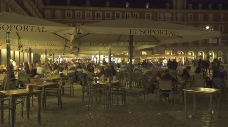 официант : Tourists have dinner at a restaurant on the Plaza Mayor, Madrid downtown, Spain