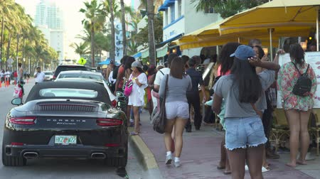 walkers : Miami beach cityscape, street view. Students and tourists walking at Ocean dr.