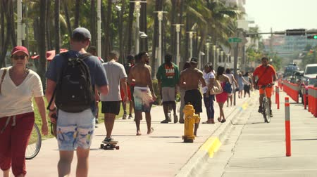 tiras : Miami beach cityscape, street view. Students and tourists walking at Ocean dr.
