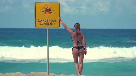 uyarmak : Sexy woman looking around on beach at warning sign - Australia