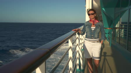 бортовой : Woman walking and stands on cruise ship deck. Girl enjoying luxury cruise liner Стоковые видеозаписи