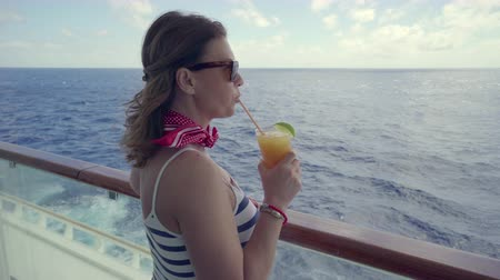 бортовой : Woman stands on balcony of cruise ship with a cocktail