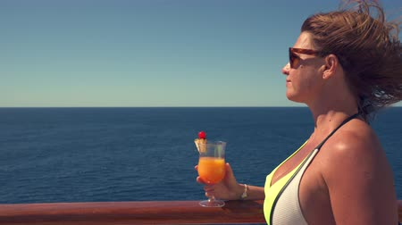 бортовой : Woman stands on cruise ship deck, drinking cocktail