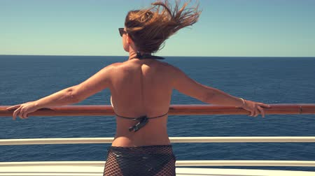 бортовой : Sexy bikini woman stands on cruise ship deck, enjoying luxury cruise liner