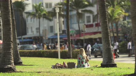 walkers : Miami beach cityscape, street view. Girl sitting in the Lummus park at Ocean dr