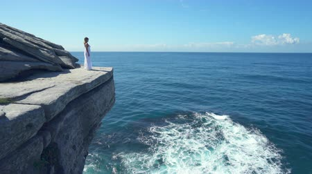 skalní útes : Beautiful woman standing on a cliff edge over the ocean.