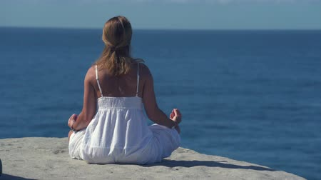 sobre o branco : Woman meditating on a cliff over the ocean, Yoga on the rock