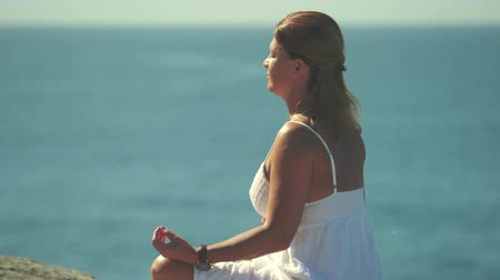 еж : Woman meditating on a cliff over the ocean, Yoga on the cliff edge Стоковые видеозаписи