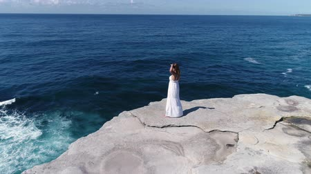 еж : Beautiful woman standing on a cliff edge over the ocean. Camera flying around