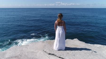 skalní útes : Beautiful woman standing on a cliff edge over the ocean. Dolly shot