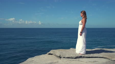 еж : Beautiful woman standing on a cliff edge over the ocean.