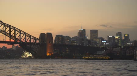 kirribilli : Sydney at sunset. Harbor Bridge and Kirribilli district with a ferry - March 2017: Sydney, Australia