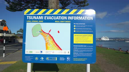 caution sign : Tsunami evacuation warning sign - March 2017: Tauranga, New Zealand Stock Footage