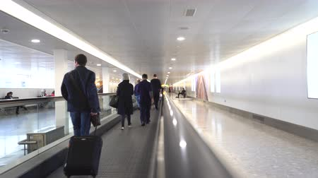 lots of : Passengers walking on a moving walkway in the airport terminal - Heathrow