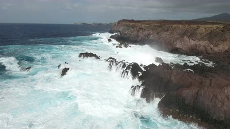 skalní útes : Aerial shot of ocean waves crashing cliff, steep coastline - Socorro Island