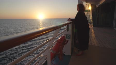 бортовой : Woman passenger stands on cruise ship deck at sunset - midnight sun