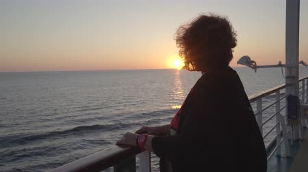бортовой : Woman passenger stands on cruise ship open deck at sunset - midnight sun