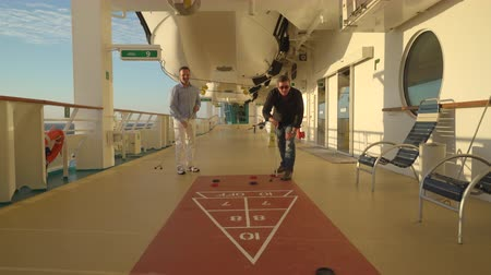 еж : Outdoor shuffleboard game on a cruise ship walking board